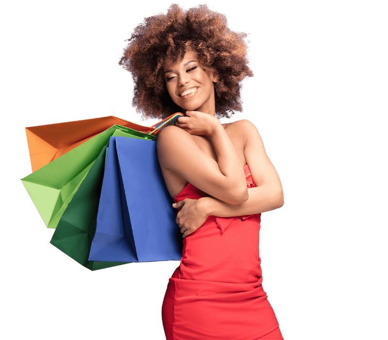 A smiling woman holding 3 shopping bags
